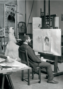 En la imagen sobre estas líneas, de c. 1899, vemos a Ramon Casas trabajando en una sesión de retratos en su estudio del paseo de Gracia. Al fondo, observamos una de las versiones del cartel taurino que realizó, en este caso anunciando una corrida en Les Arènes de Nimes.